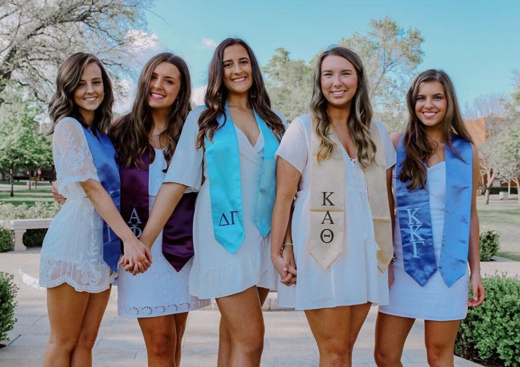 Five women standing together wearing white dresses and stoles for their respective sororities