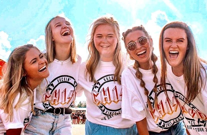 Five women wearing Chi Omega shirts for Bid Day.