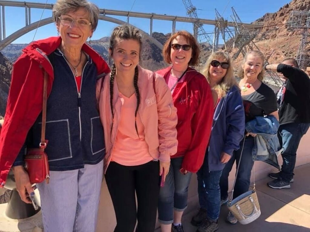A group of sorority alumnae standing together outside near a bridge.