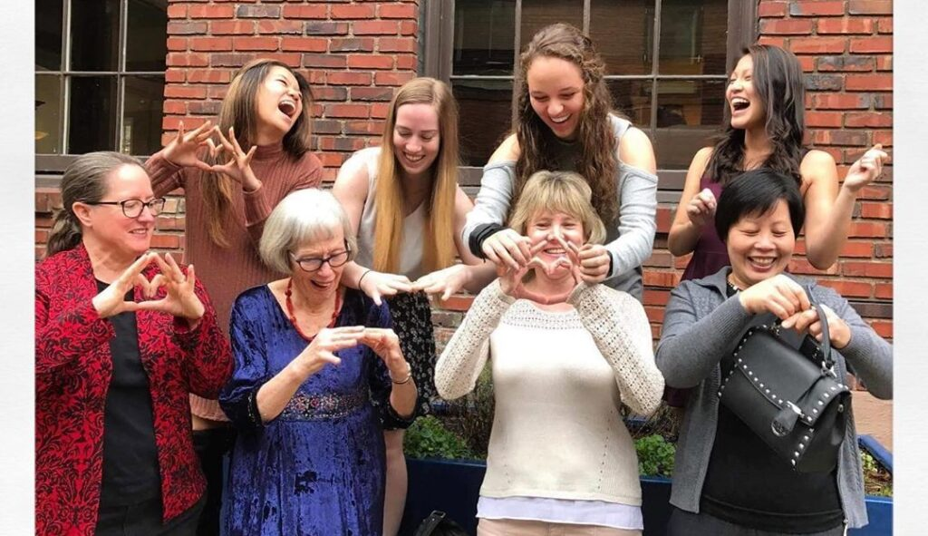 A group of sorority women showing their mothers how to throw their sorority hand sign.